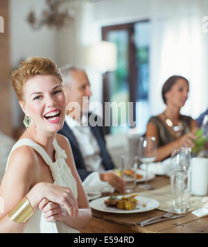 Woman laughing at dinner party - Stock Photo