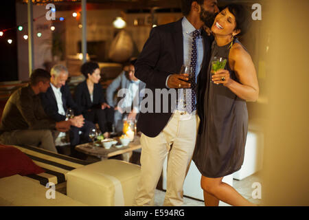 Couple kissing at party - Stock Photo