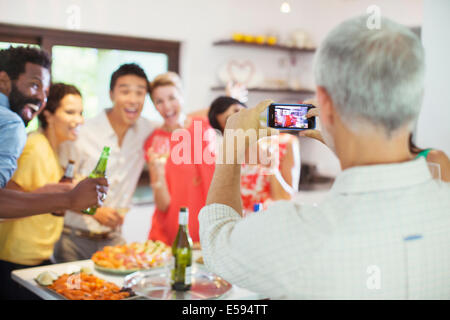 Friends taking picture together at party - Stock Photo