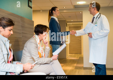 Male doctor shaking hands with his patient in waiting room - Stock Photo