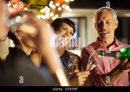 Friends drinking champagne at party - Stock Photo