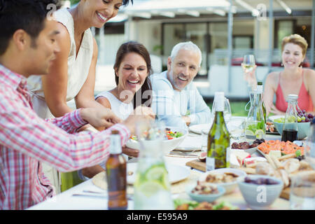 Woman serving friends at party - Stock Photo