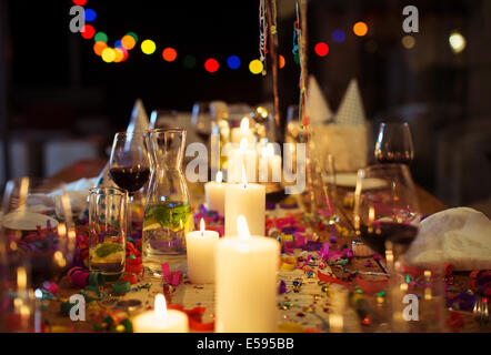 Lit candles on table at party - Stock Photo