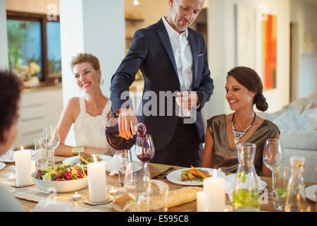Man pouring wine at dinner party - Stock Photo