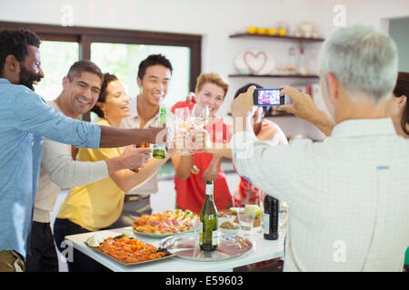 Man taking picture of friends at party - Stock Photo