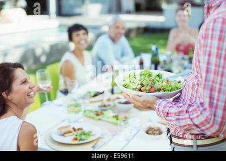 Man serving friends at table outdoors - Stock Photo