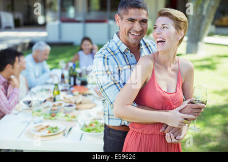 Laughing couple hugging outdoors - Stock Photo