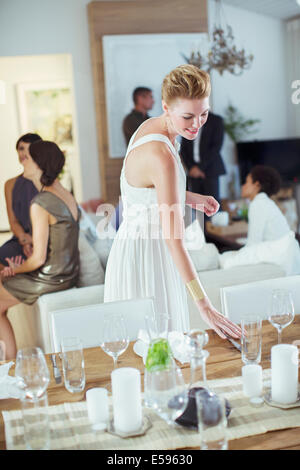 Woman setting table at dinner party - Stock Photo