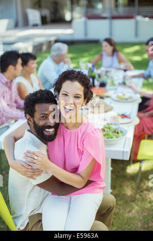 Couple hugging at table outdoors - Stock Photo