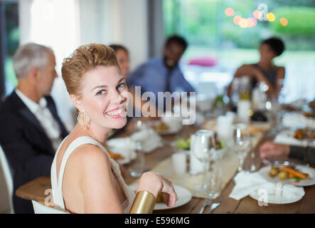 Woman smiling at dinner party - Stock Photo