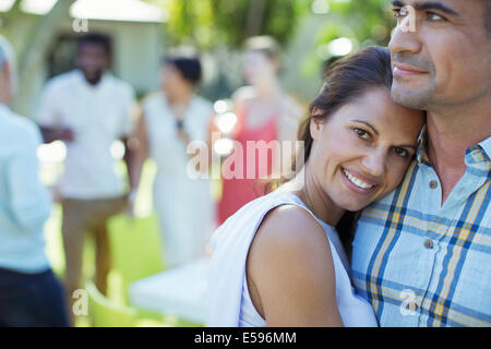 Couple hugging at dinner party - Stock Photo