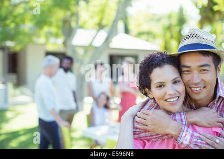Couple hugging at party - Stock Photo