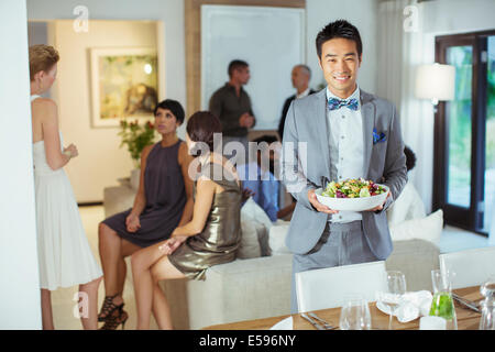 Man serving food at dinner party - Stock Photo
