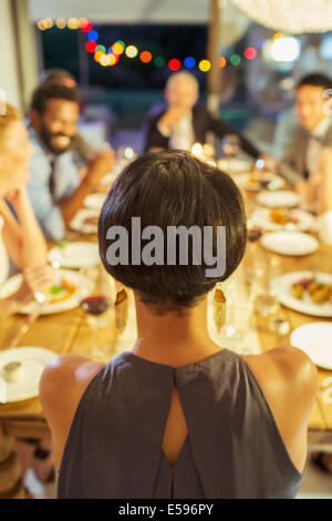 Woman sitting at dinner party - Stock Photo