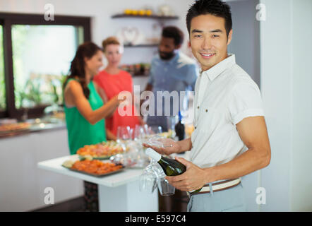 Man carrying bottle of wine at party