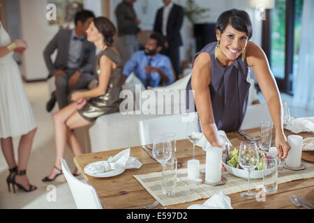 Woman serving food at dinner party - Stock Photo