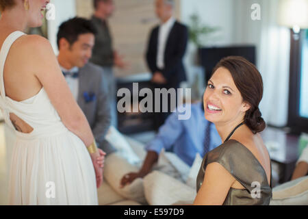 Woman smiling on sofa at party - Stock Photo