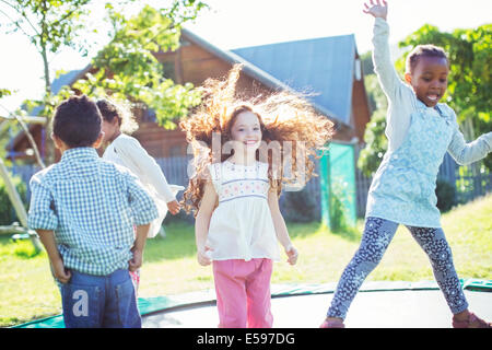 Children jumping on trampoline outdoors - Stock Photo