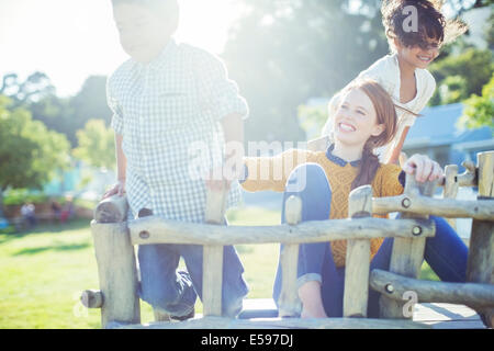 Babysitter and children playing outdoors - Stock Photo