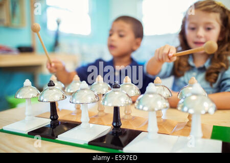 Students playing bells in class - Stock Photo