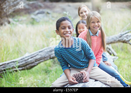 Children sitting on log in forest - Stock Photo