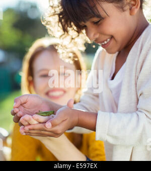 Mother and daughter examining insect