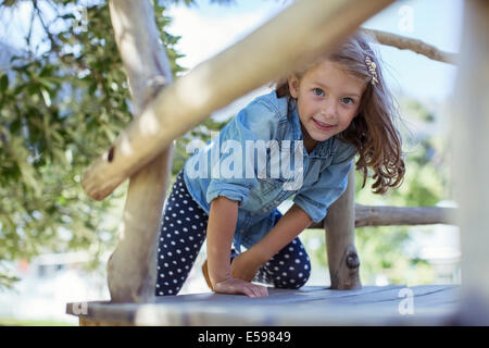 Girl climbing in treehouse outdoors - Stock Photo