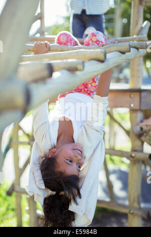 Girl climbing on monkey bars on playground - Stock Photo