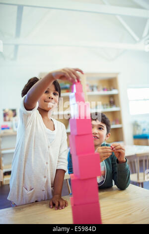 Students stacking blocks in classroom - Stock Photo