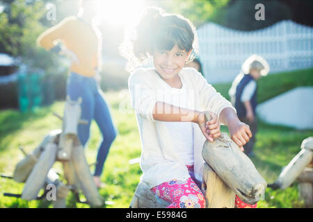 Girl smiling on rocking horse in playground - Stock Photo
