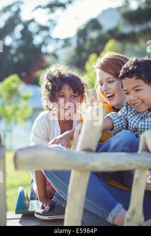 Students and teacher sitting outdoors - Stock Photo