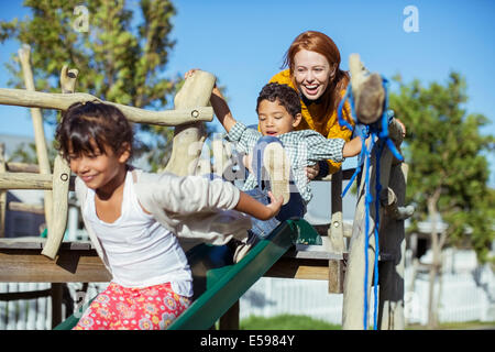 Teacher and students playing on playground - Stock Photo