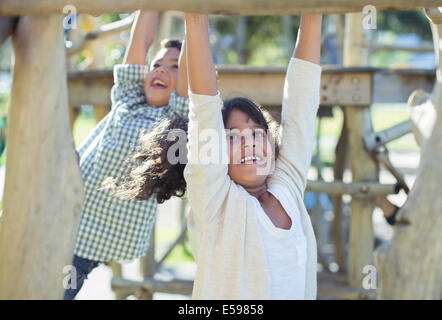 Children climbing on monkey bars - Stock Photo
