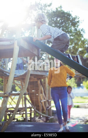 Teacher watching student play on play structure - Stock Photo