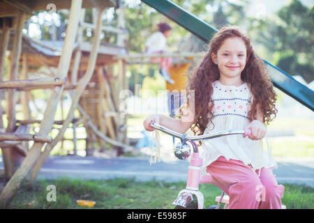 Smiling girl sitting on bicycle at playground - Stock Photo
