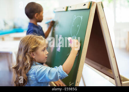 Students drawing on chalkboard in classroom - Stock Photo