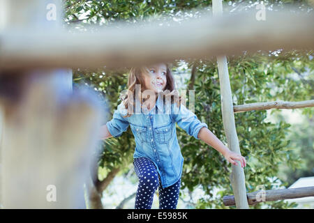 Girl climbing on play structure - Stock Photo
