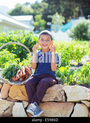 Boy with basket of produce in garden - Stock Photo