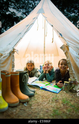 Children smiling in tent at campsite - Stock Photo
