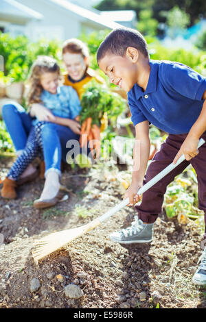 Boy turning over soil in garden - Stock Photo