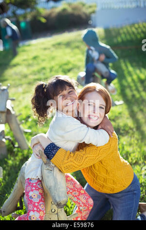 Student and teacher hugging outdoors - Stock Photo