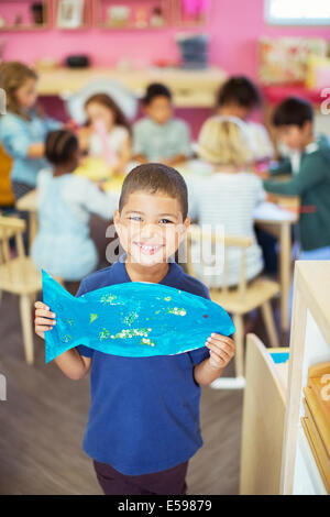 Student holding painted fish in classroom - Stock Photo