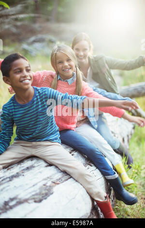 Students and teacher sitting on log in forest - Stock Photo