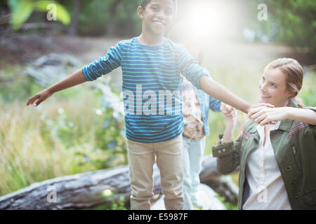Teacher and student playing in forest - Stock Photo