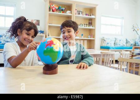 Students examining globe in classroom - Stock Photo