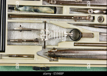Old drawing tools in a box on a green background - Stock Photo