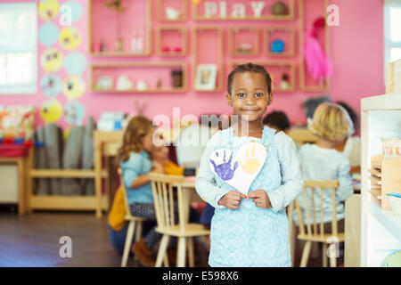 Student holding painting in classroom - Stock Photo