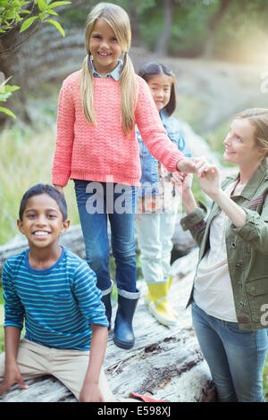 Students and teacher climbing on log - Stock Photo