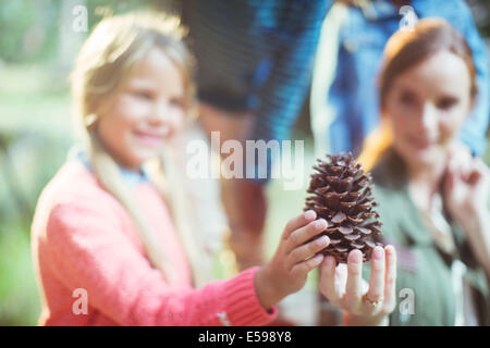Students and teacher holding pine cone in forest - Stock Photo