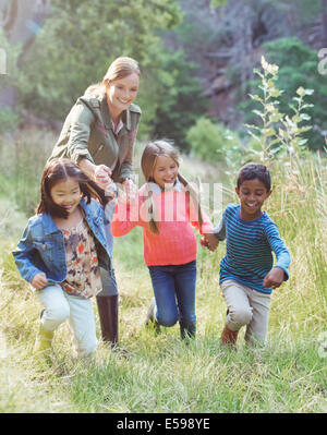 Students and teacher walking in field - Stock Photo